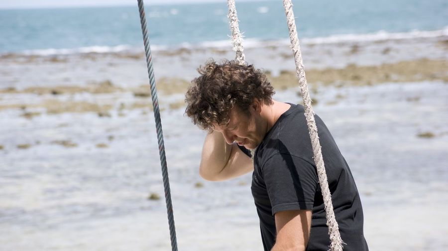 Side view of young man swinging at beach