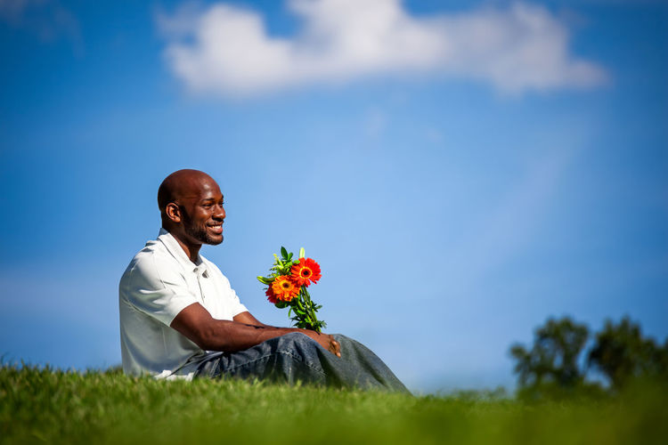 Smiling Man Sitting With Flowers On Grass Against Blue Sky