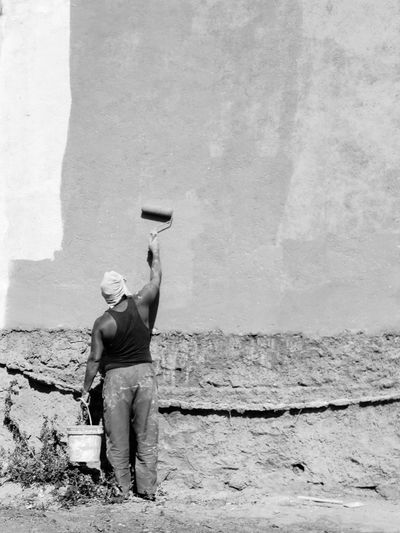 Rear view of man working on wall