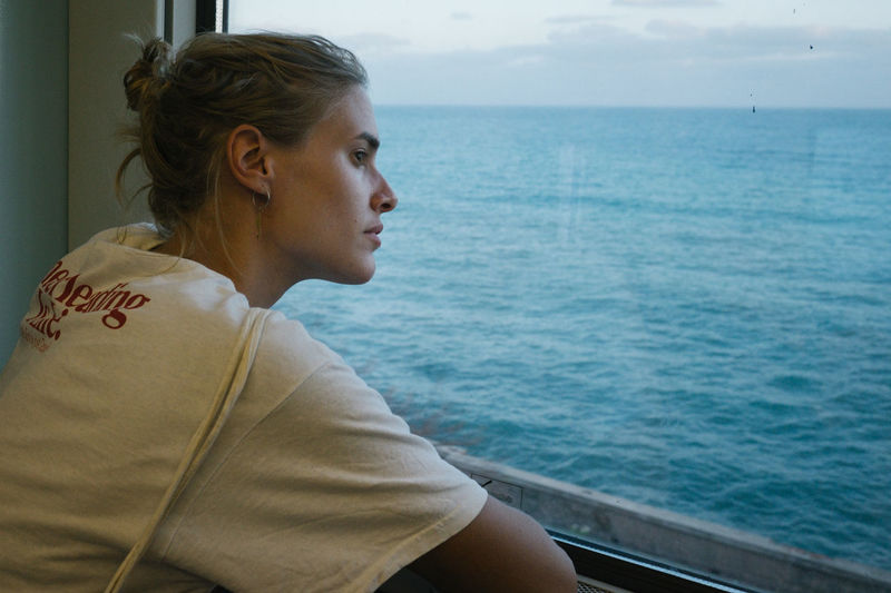 Young woman looking through window in boat against sea
