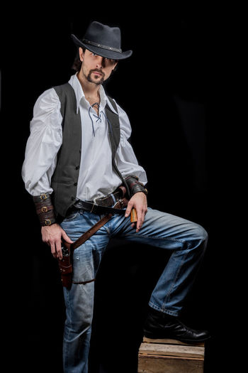 Handsome young man. This is an American cowboy. A vow to a white shirt, brown waistcoat and blue jeans. Black shoes on the feet. Carries a shtyapa, on a belt two pistols. The hair is of medium length; on the face is a beard and mustache. Authentic photo. Culture of America. Cowboy Wild West America American Gun National Authentic Moments Lifestyles Lifestyle One Person Candid Authentic Three Quarter Length Hat Clothing Front View Black Background Holding Men Weapon Handgun Young Adult Adult Young Men Jeans