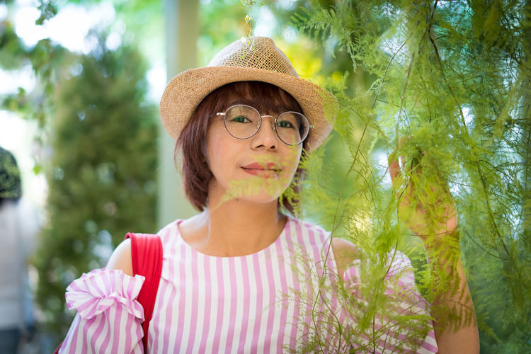 woman with hat posting in the garden Portrait Hat Front View One Person Plant Headshot Looking At Camera Glasses Smiling Women Day Clothing Nature Focus On Foreground Tree Fashion Adult Casual Clothing Leisure Activity Sun Hat Outdoors Hairstyle