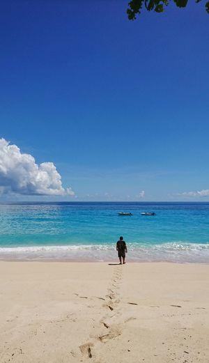 Man on beach against blue sky