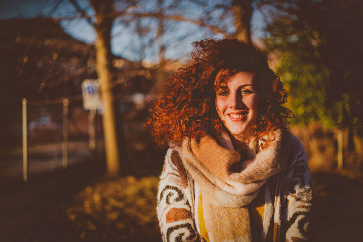 Portrait Of Smiling Young Woman Standing Against Trees During Sunny Day