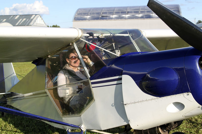 Beautiful woman sitting in propeller airplane