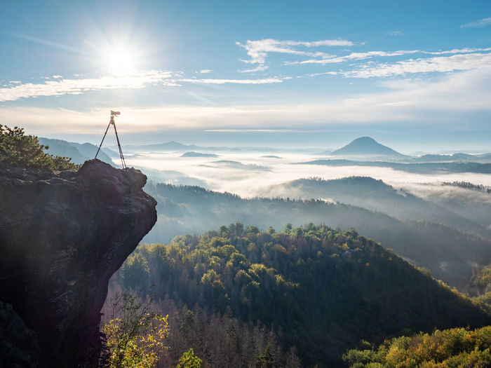 Camera stand on tripod photographing mountain, blue sky and foggy landscape. mountains background