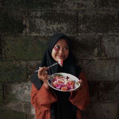 Woman wearing hijab eating food against wall