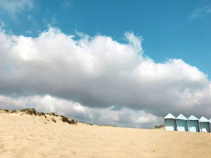 Low Angle View Of Beach Against Cloudy Sky
