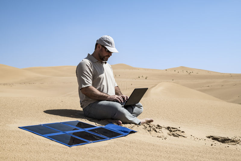 Adult (man) working with his computer in the Middle of the dunes by clear sky, using portable flexible solar panels and charger Alone Desert Dubai Going Remote Man Middle East Nature Sahara Desert Solar Panel Working Alone... Arid Climate Arid Landscape Computer Day Ecology Electricity  Energy Environment Laptop Material Remote Sun Travel Destinations Wireless Technology
