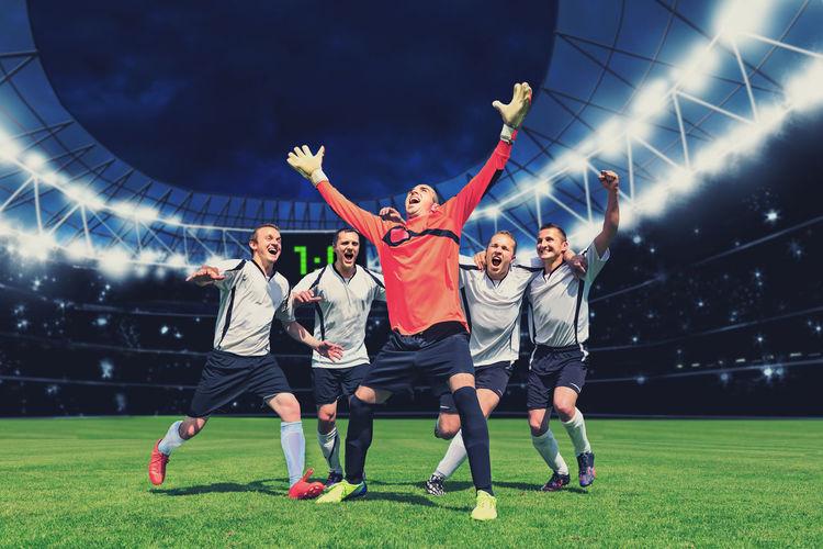 Men celebrating soccer on field