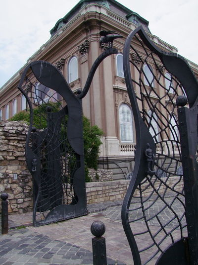 Modern Spiders Web Gates, Royal Palace Budapest Castle Hill Cloudy Sky Fun Gate Hungary Tourist Attraction  Unusual Building Exterior Bush Capital City Corner Of Building History Low Angle View No People Palace Royal Palace Spiders Web Travel Destination Wrought Iron Gate