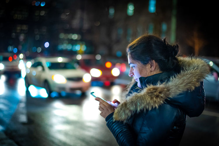 Woman holding mobile phone on street in city during winter