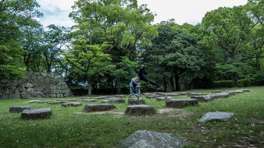 Full length of person breakdancing on rock in garden