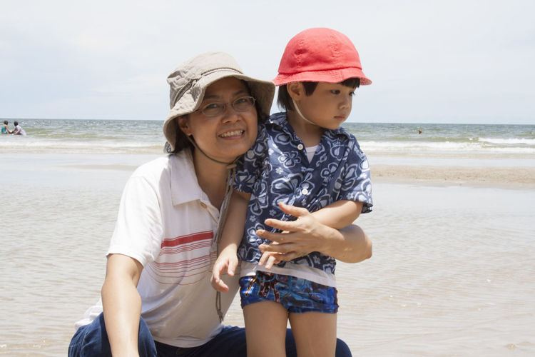 Smiling happy mother holding boy at beach