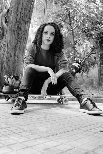 Portrait of young woman sitting on tree trunk in park