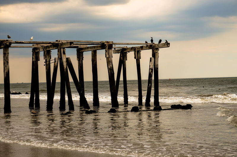 Abandoned wooden pier at beach against sky