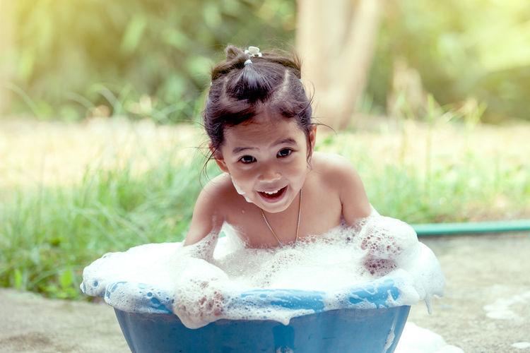 Portrait Of Happy Girl Taking Bath In Backyard