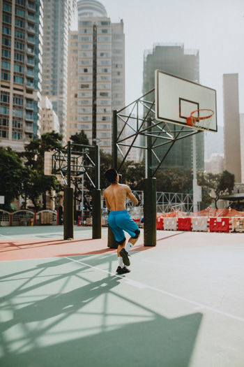 Full length of man playing basketball against buildings in city