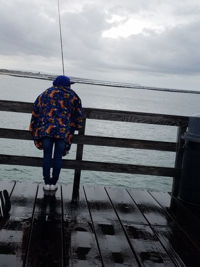 Natural Light No Edit Fishing Wet And Cold Drizzling Rainy Day Alone Dramatic Sky Water Sea Clouds Sky Drama EyeEm Nature Lover EyeEm Best Shots Fine Art Photography Distance Nature Beauty In Nature Copy Space One Person Lifestyles Tranquility Leisure Activity Outdoors