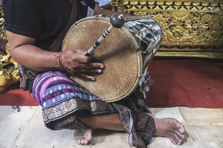 Low section of man playing tabla on floor