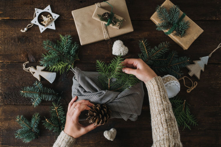 Directly above shot of woman holding christmas decoration on table