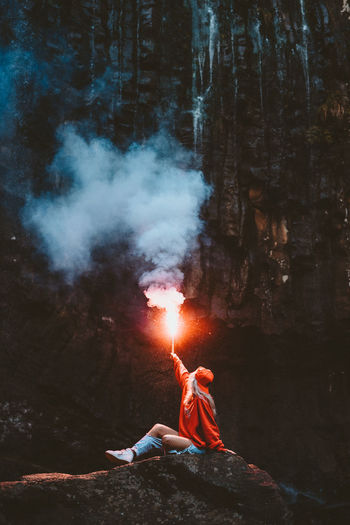 Woman Holding Distress Flare While Sitting In Forest