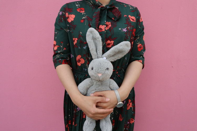 Midsection Of Woman Holding Stuffed Toy Against Pink Wall