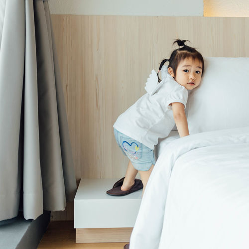 Portrait Of Girl Climbing On Bed