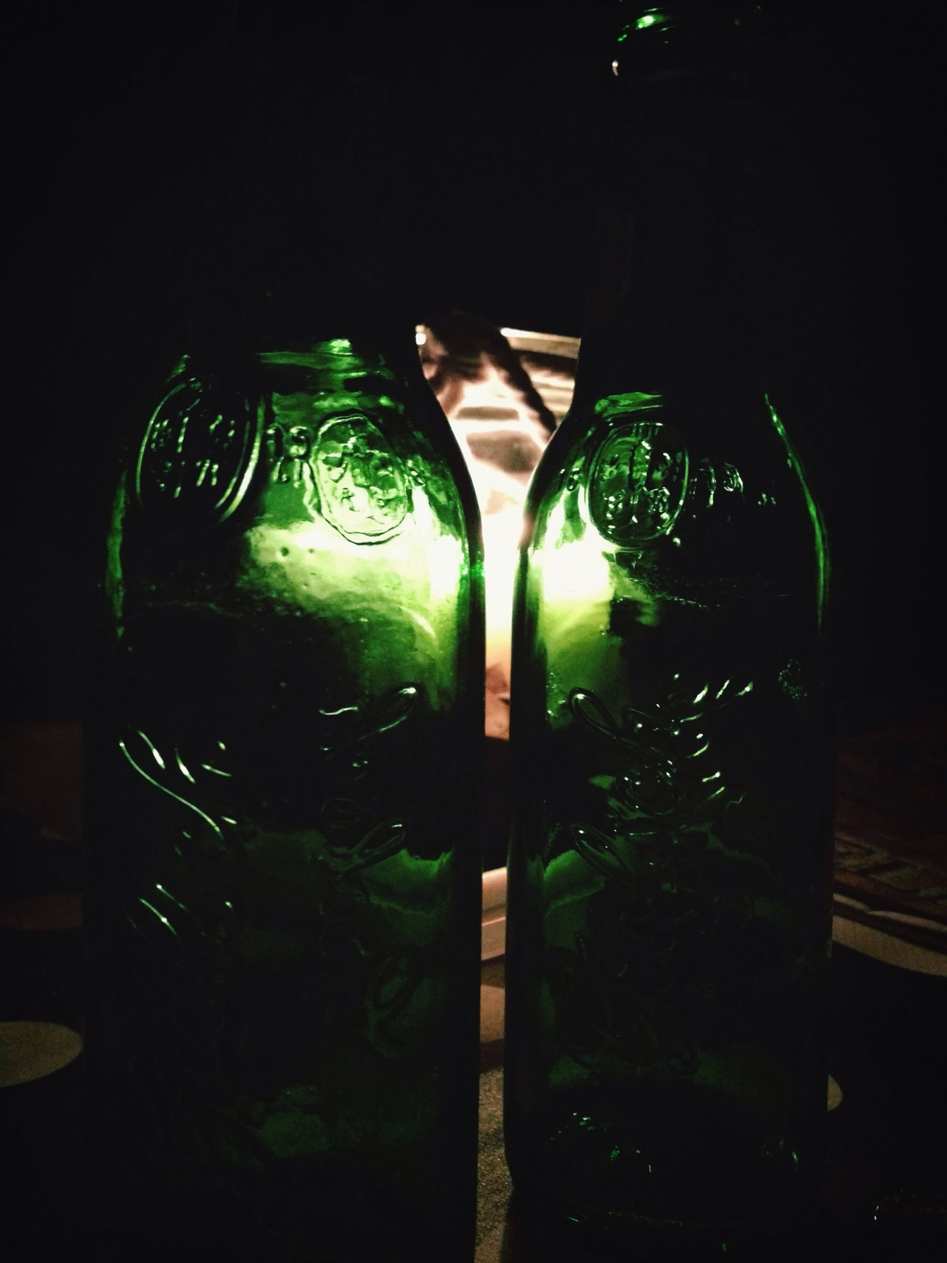indoors, glass - material, still life, table, green color, close-up, transparent, no people, illuminated, home interior, bottle, glass, wall - building feature, potted plant, drinking glass, shadow, decoration, plant, vase, growth