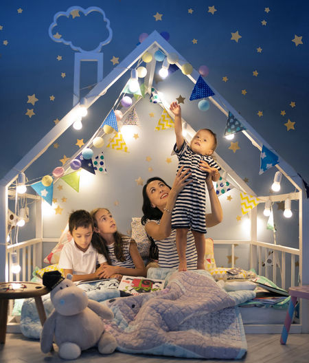 Portrait of a family with mom and three children reading bed time stories Fairytale  Bed Time Stories Bonding Casual Clothing Child Childhood Daughter Family Girls Good Night Group Of People Happyness Illuminated Indoors  Innocence Leisure Activity Lifestyles Pajamas Real People Sister Smiling Togetherness Women