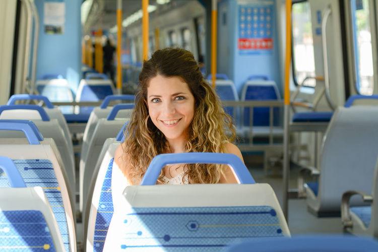 Portrait of smiling man sitting in train