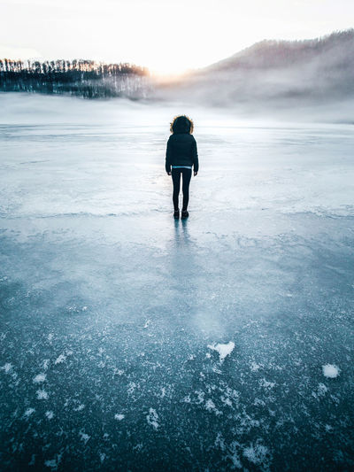 Full Length Rear View Of Woman Standing On Frozen Lake