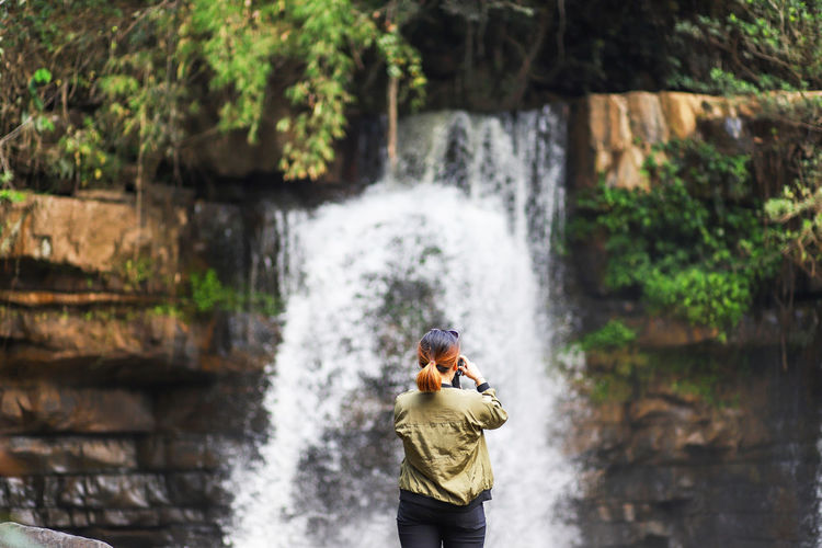 Rear view of woman photographing waterfall