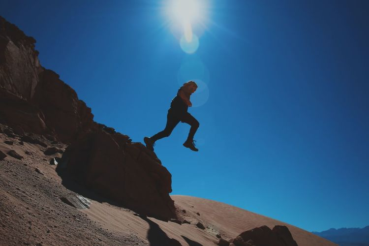 Low angle view of man jumping over desert on sunny day