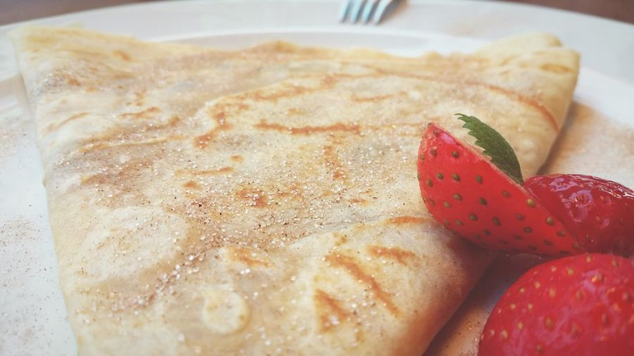 Close-up of fresh pancake and strawberries served in plate