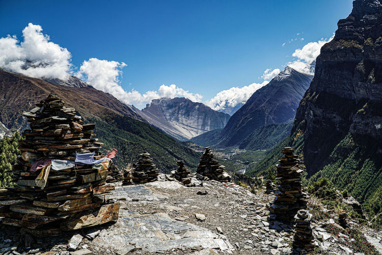 Stack of rocks on snowcapped mountains against sky