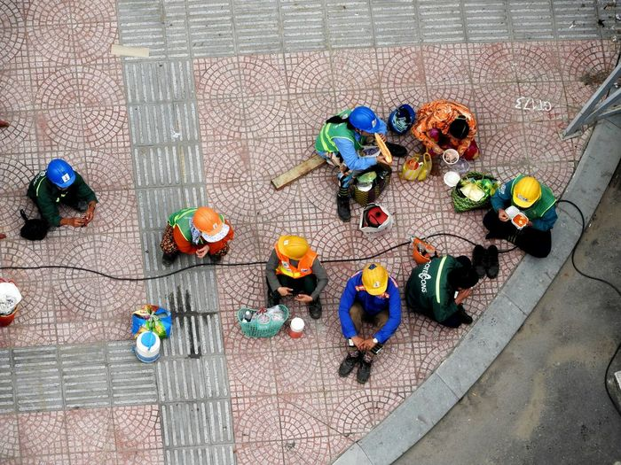 Directly above shot of workers sitting on walkway