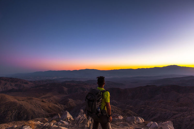 Rear view of man standing on mountain against clear blue sky during sunset