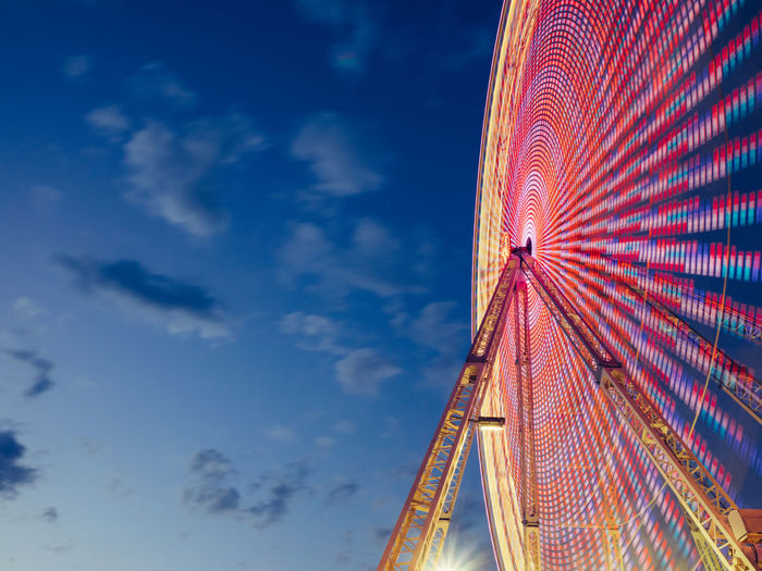 In Motion Amusement Park Ride Big Wheel Blue Cloud Cloud - Sky Funfair Lights Long Exposure Low Angle View Modern Multi Colored No People Outdoors Sky Tall - High