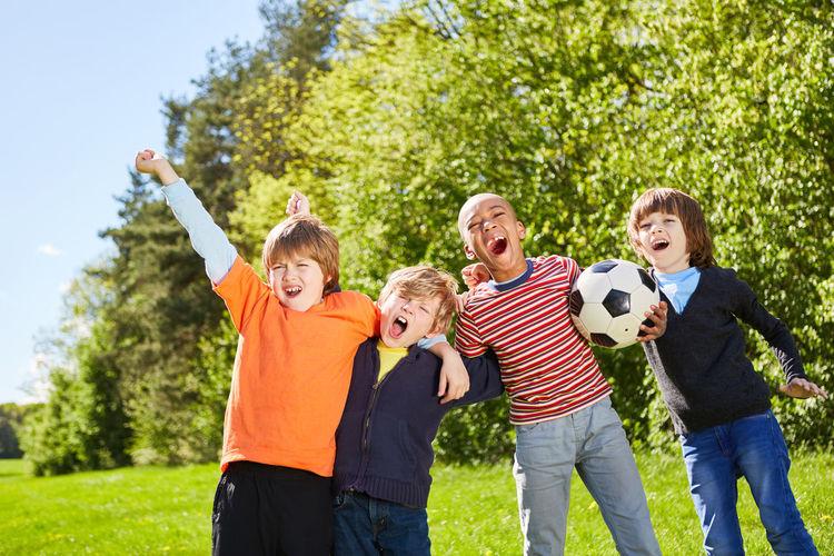 Full length of children on soccer field against plants