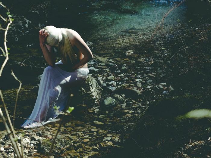 Woman sitting on rock in lake
