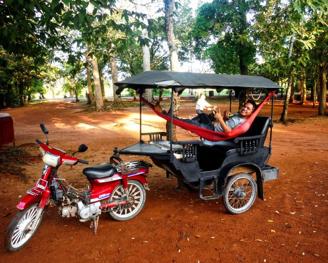 While we spend hours exploring the Angkor Wat wonders, our Tuk Tuk driver Johnny snoozes the day away in this ingenious set-up. Hammock Life Chill Mode Relaxing Nap Time Asian Culture TukTuk Motorbike Hammock Chilling Relaxed Easy Living Enjoying Life Content Angkor Wat, Cambodia Cambodia Tourism Relaxation Hammock Time Tuktuk Driver Chillin' Resting Fujifilm Finepix Xp60