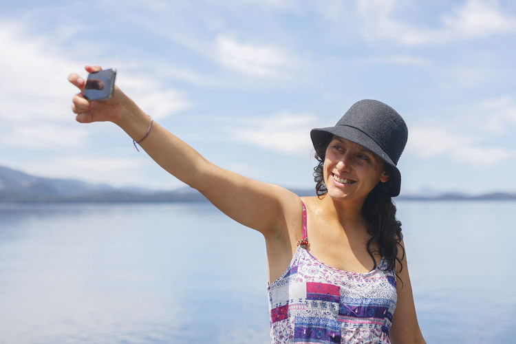 Young woman takes a photo of herself, which we call selfie Adult Beach Beauty In Nature Canon_photos Cheerful Day Happiness Human Body Part Landscape Nature One Person Outdoors People Portrait Selfie Selfie Portrait Sky Smiling Travel Destinations Vacations Water Young Adult