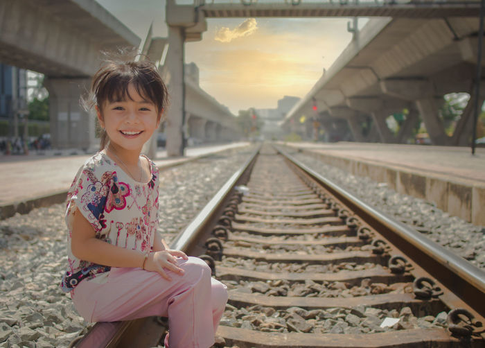 Portrait of girl sitting on railroad track