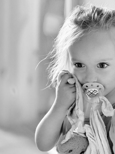 Close-Up Of Girl With Pacifier At Home