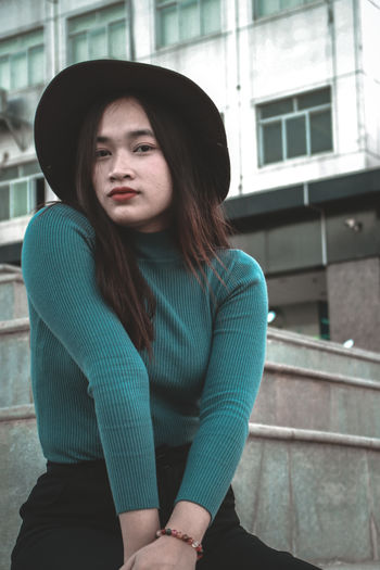 Portrait of beautiful woman wearing hat sitting on steps