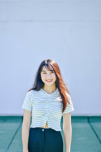 Portrait of young woman smiling while standing against wall