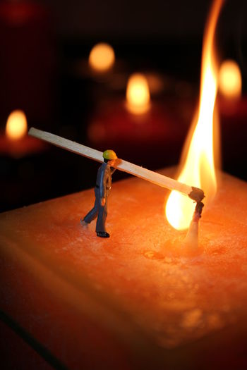 Close-Up Of Figurine Lighting Candle