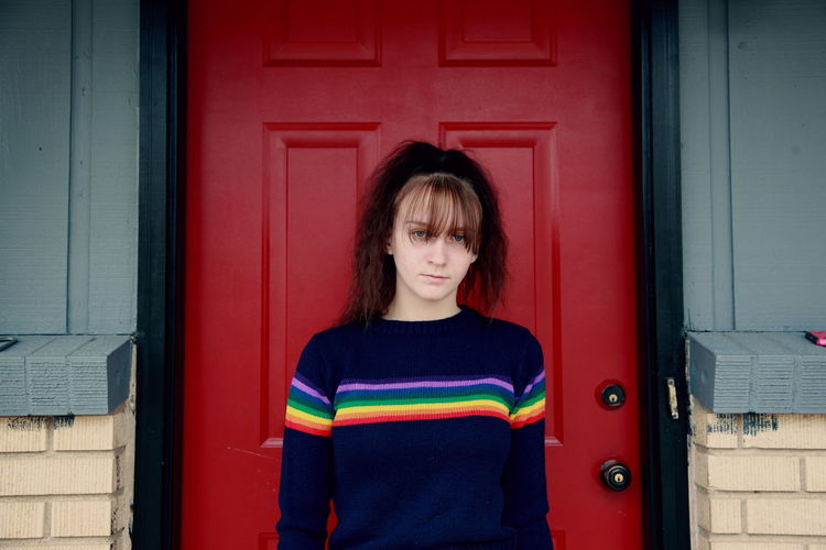 Portrait Of Teenage Girl Standing By Red Door