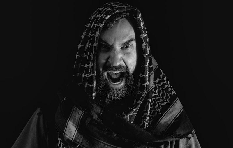Man shouting against black background